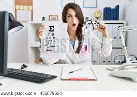 Young doctor woman holding optometry glasses and eyesight test at the clinic in shock face, looking skeptical and sarcastic, surprised with open mouth