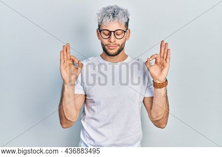 Young hispanic man with modern dyed hair wearing white t shirt and glasses relaxed and smiling with eyes closed doing meditation gesture with fingers. yoga concept.