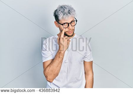 Young hispanic man with modern dyed hair wearing white t shirt and glasses pointing to the eye watching you gesture, suspicious expression