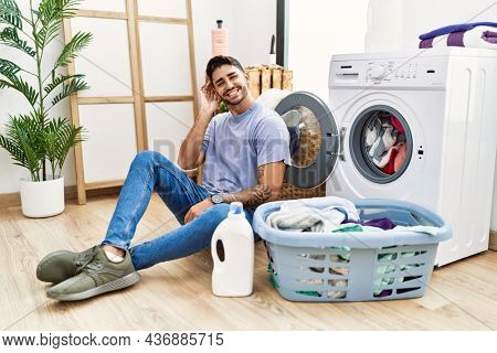 Young hispanic man putting dirty laundry into washing machine smiling with hand over ear listening an hearing to rumor or gossip. deafness concept.