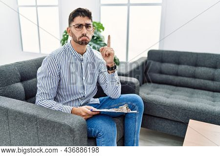 Young psychologist man at consultation office pointing up looking sad and upset, indicating direction with fingers, unhappy and depressed.