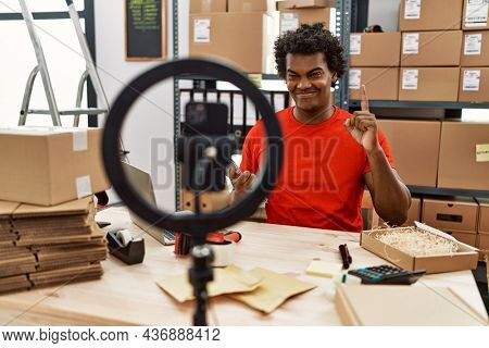 African man working at small business ecommerce doing video tutorial surprised with an idea or question pointing finger with happy face, number one