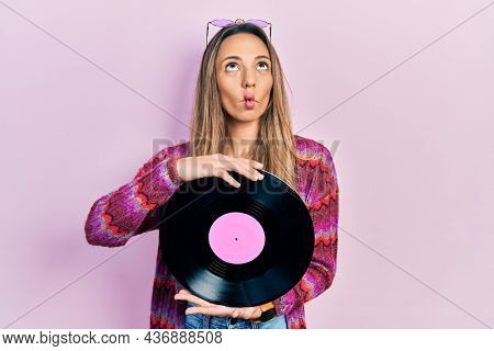 Beautiful hispanic woman wearing hippie style holding vinyl disc making fish face with mouth and squinting eyes, crazy and comical.