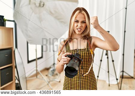 Young caucasian photographer girl holding professional camera at photography studio annoyed and frustrated shouting with anger, yelling crazy with anger and hand raised