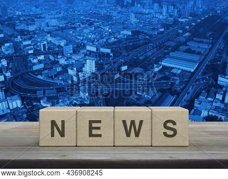 News Letter On Wood Block Cubes On Wooden Table Over Modern City Tower, Street, Expressway And Skysc