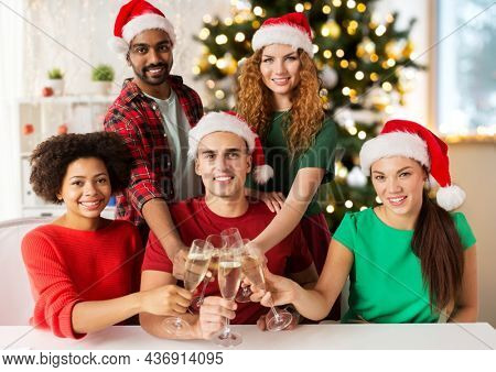 christmas, celebration and holidays concept - happy team in santa hats clinking glasses of non-alcoholic champagne at corporate office party over christmas tree background