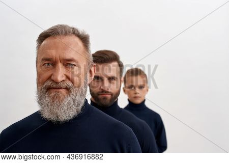 Portrait Of Three Generations Of Caucasian Men. Old Grey-haired Grandfather Forefront, Adult Young S