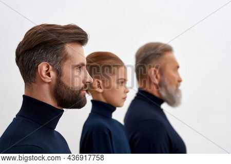 Young Man Forefront, Small Son And Senior Father Back. Faces Of Three Generations Of Men Isolated On