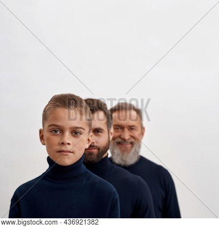 Narrow Shot Portrait Of Three Generations Of Caucasian Men In Row Isolated On White Studio Backgroun