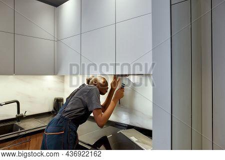 Young Woman Handyman Examining Kitchen Exhaust With Flashlight. Modern Minimalistic Design Kitchen.