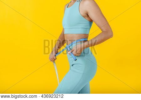Beautiful Slim Woman In Sportswear Measures Her Belly Or Waist With A Tape. Diet And Sport Concept
