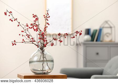 Hawthorn Branches With Red Berries On Wooden Table In Living Room