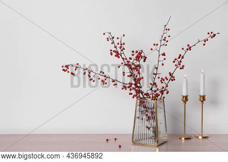 Hawthorn Branches With Red Berries In Vase And Candles On Wooden Table, Space For Text