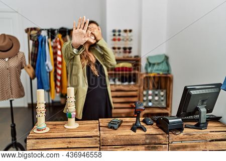 Beautiful hispanic woman working at fashion shop covering eyes with hands and doing stop gesture with sad and fear expression. embarrassed and negative concept.