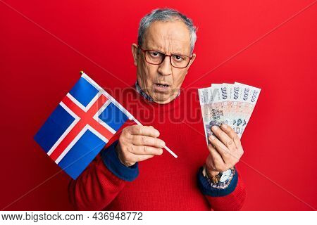 Handsome senior man with grey hair holding iceland flag and icelandic krona banknotes in shock face, looking skeptical and sarcastic, surprised with open mouth