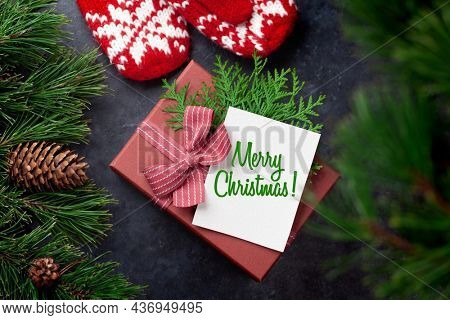 Christmas gift box with craft decor and Merry Christmas greeting card. Top view flat lay