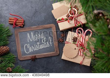 Christmas gift boxes with craft decor and chalkboard with Merry Christmas greetings. Top view flat lay
