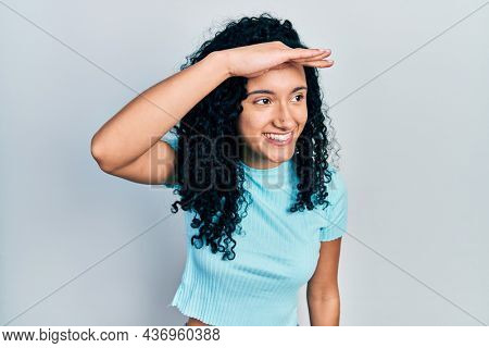 Young hispanic woman with curly hair wearing casual blue t shirt very happy and smiling looking far away with hand over head. searching concept.