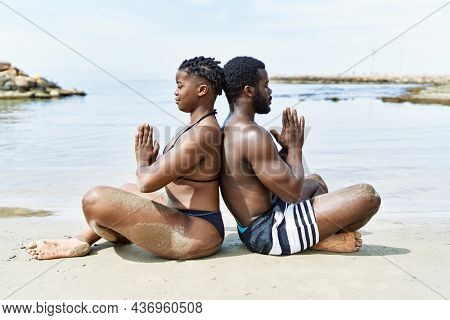 Young african american tourist couple wearing swimwear meditating doing yoga exercise at the beach.
