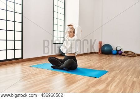 Young blonde girl concentrated stretching at sport center.