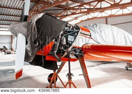 Ultralight small private aircraft airplane on repair in the hangar at the aerodrome airport
