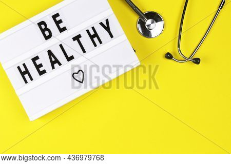 Lightbox With Words Be Healthy And Stethoscope On Yellow Colored Background. Care Of Health And Medi