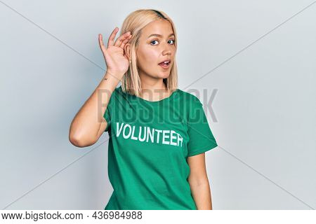 Beautiful blonde woman wearing volunteer t shirt smiling with hand over ear listening an hearing to rumor or gossip. deafness concept.