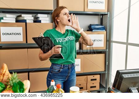 Young brunette woman wearing volunteer t shirt at donations stand shouting and screaming loud to side with hand on mouth. communication concept.