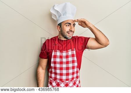 Young hispanic man wearing baker uniform very happy and smiling looking far away with hand over head. searching concept.