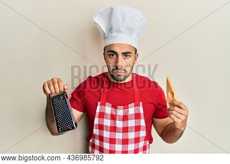 Young hispanic man wearing professional cook uniform holding grater and cheese depressed and worry for distress, crying angry and afraid. sad expression.