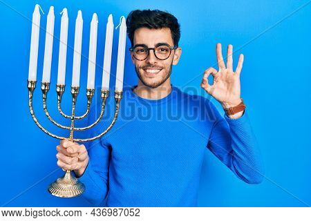 Young hispanic man holding menorah hanukkah jewish candle doing ok sign with fingers, smiling friendly gesturing excellent symbol