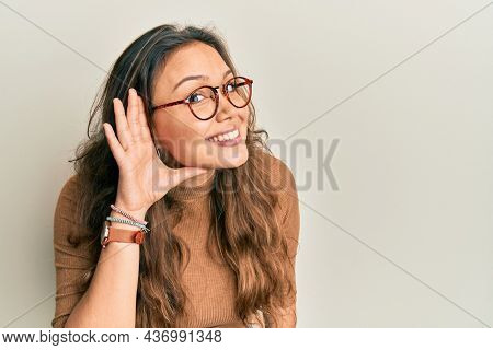 Young hispanic girl wearing casual clothes and glasses smiling with hand over ear listening an hearing to rumor or gossip. deafness concept.