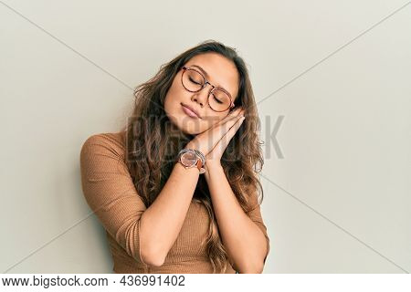 Young hispanic girl wearing casual clothes and glasses sleeping tired dreaming and posing with hands together while smiling with closed eyes.