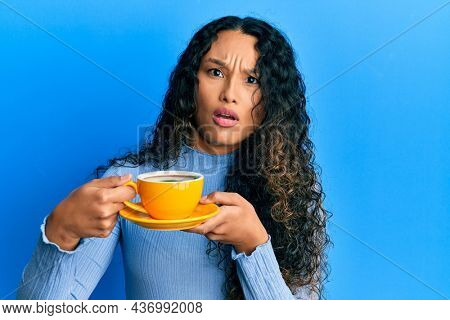 Young latin woman holding coffee in shock face, looking skeptical and sarcastic, surprised with open mouth