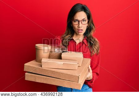 Young latin woman holding take away food in shock face, looking skeptical and sarcastic, surprised with open mouth