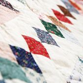 A detail photo of hand stiching on patchwork quilt poster