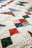 A detail of a hand sewn patchwork quilt poster