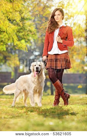 Smiling young woman with her labrador retreiver dog in a park