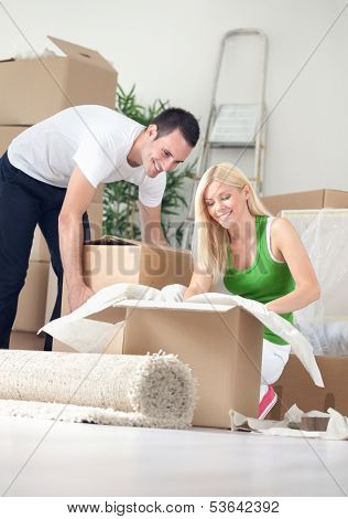 Cheerful couple in new home, unpacking boxes