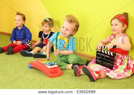 Two girls and two boys sitting at the bright walls, a boy playing on the metallophone