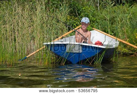 A young caucasian fisherman is fishing from a boat