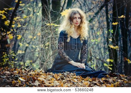 Young Pretty Woman Sits In The Wood