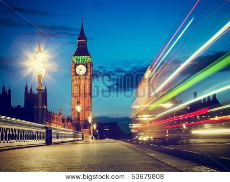 London, the UK. Red bus in motion and Big Ben, the Palace of Westminster at night. The icons of England