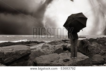 girl with umbrella on the ocean shore, melancholia concept