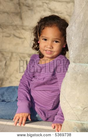 Toddler Sitting On A Rock Wall