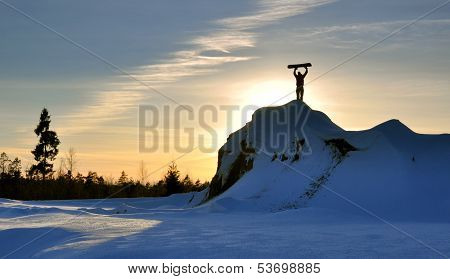Snowboarder reaches the top of a snowy mountain