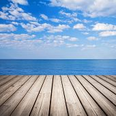 Empty wooden pier with sea and cloudy sky on background poster