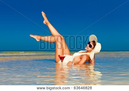 young woman in straw hat laying at the tropical beach and enjoying cocktail poster
