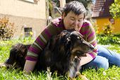 mentally disabled woman is lying with dog on a lawn poster