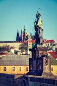 Vintage retro hipster style travel image of John of Nepomuk national saint of the Czech Republic statue on Charles Brigde at site where saint was thrown into Vltava with St. Vitus Cathedral in Prague poster
